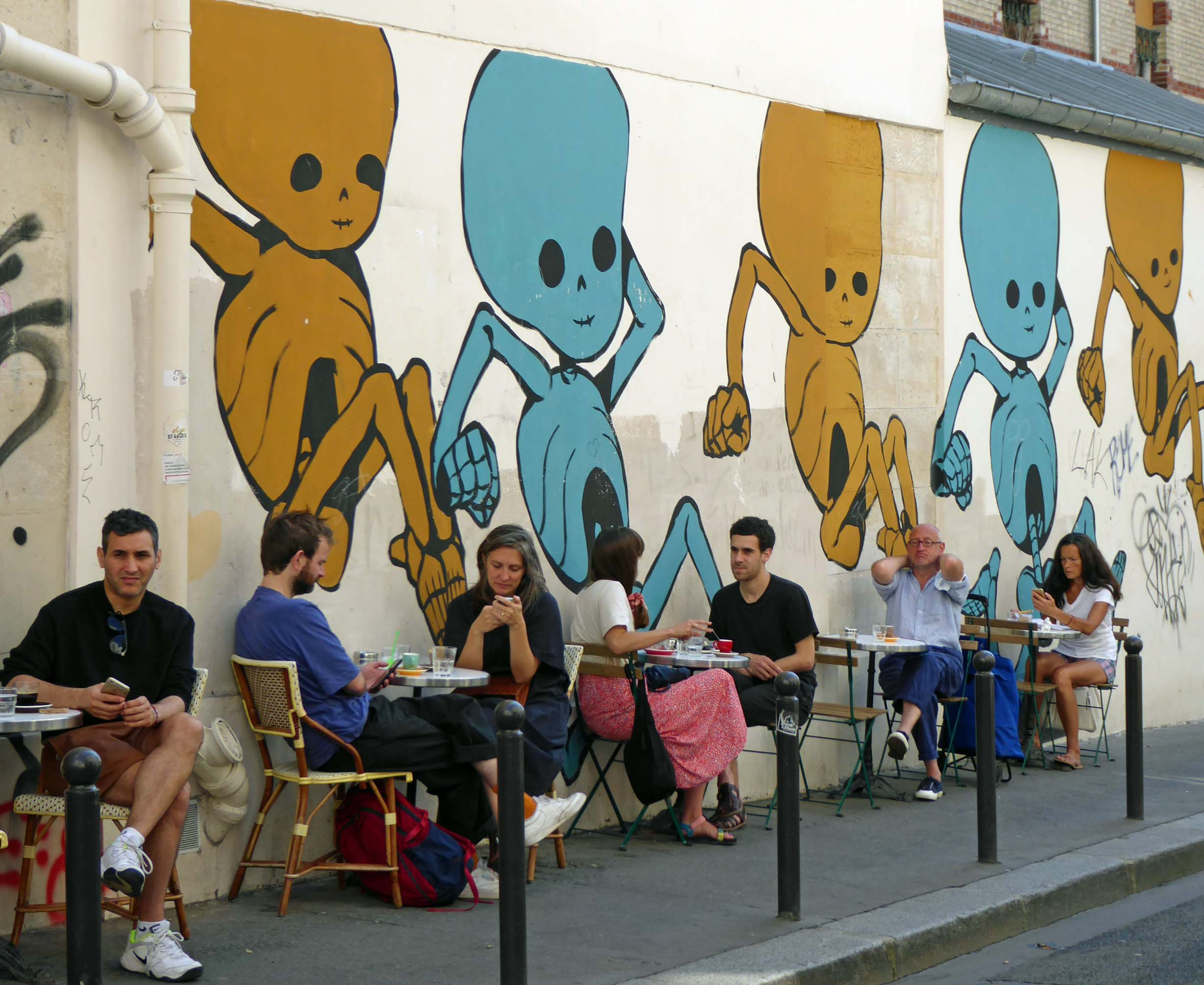 Couples sitting at tables by a painted wall