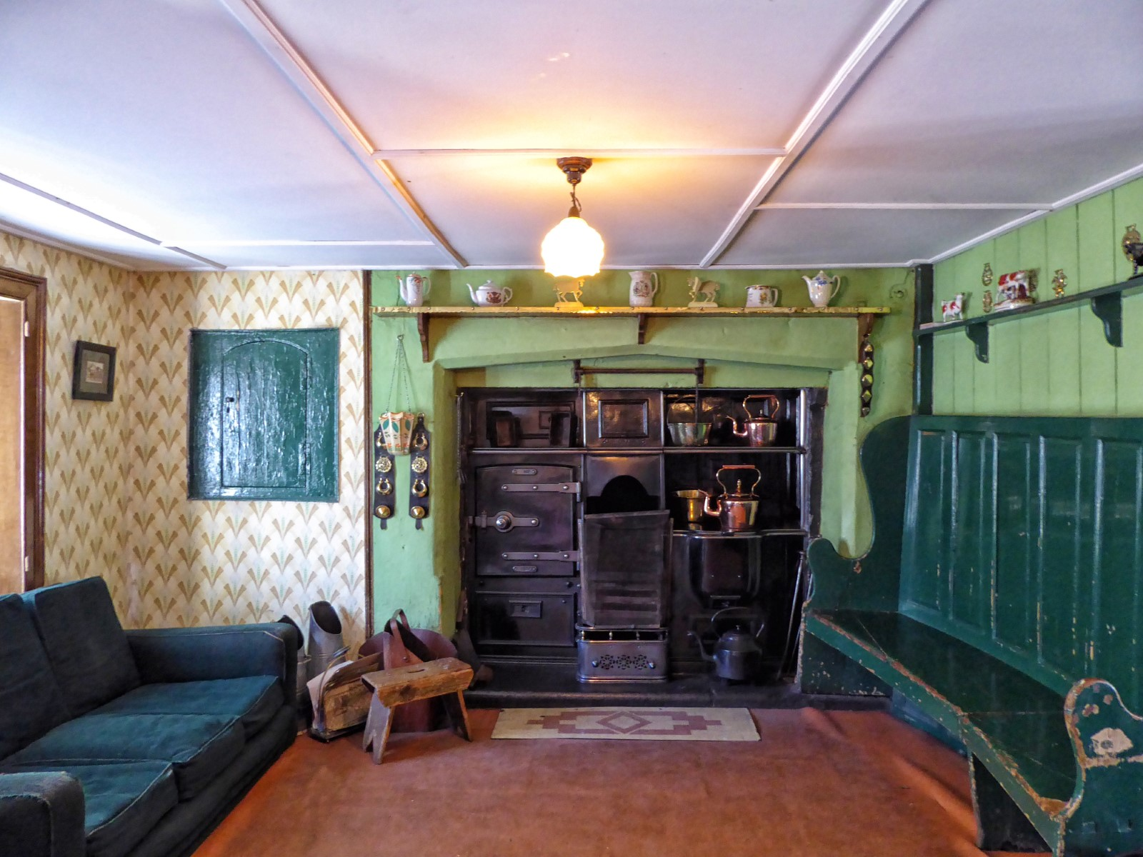 Old-fashioned room with range and green wood furniture