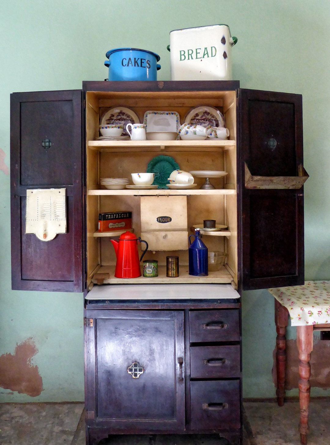 Old-fashioned cupboard with plates and utensils
