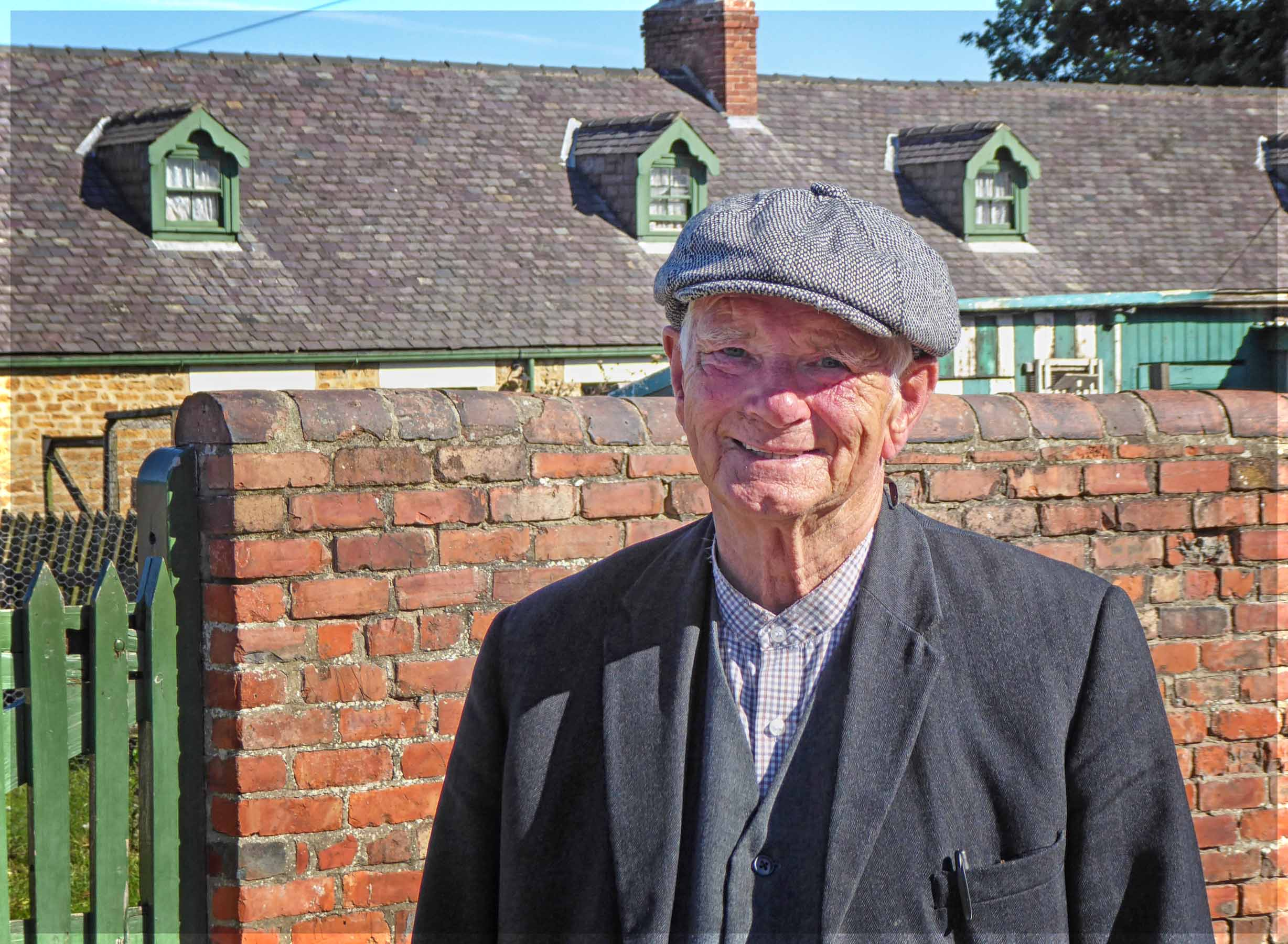Man in cloth cap in front of row of cottages