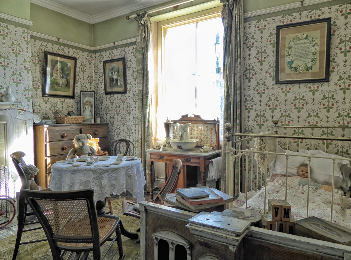 Old-fashioned bedroom with fancy wallpaper and lots of lace