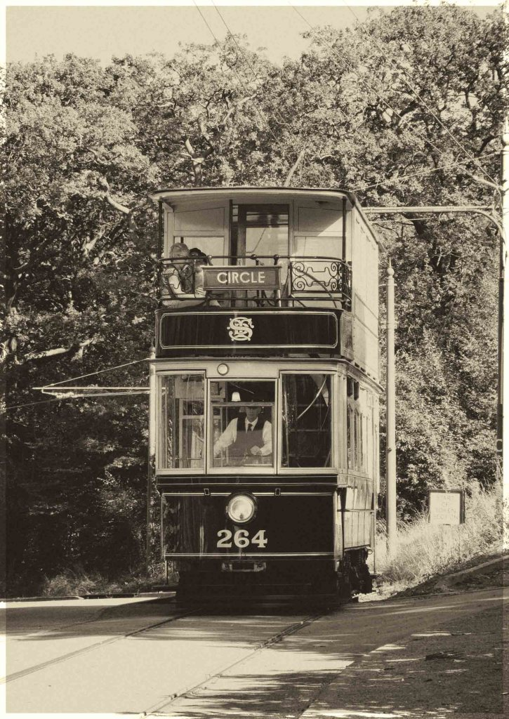 Sepia photo of a tram approaching with trees beyond