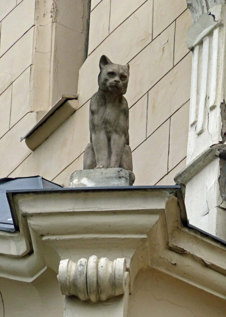 Sculpture of a small black cat on a building