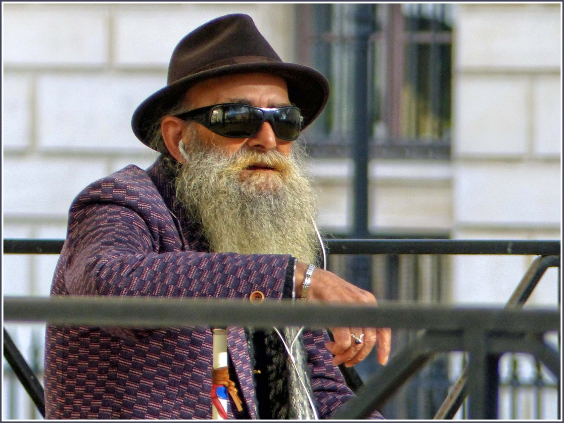 Man with a long beard, sunglasses and hat