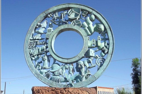 Sculpture of a bronze wheel decorated with figures, buildings etc