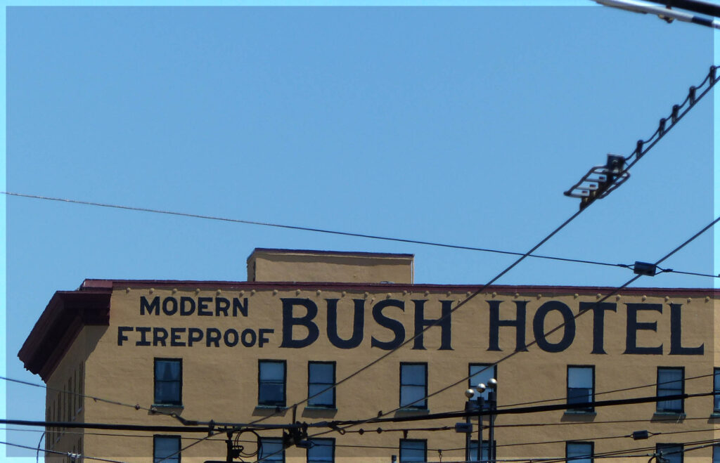 """Building with sign """"Bush Hotel"""" and tramlines"""