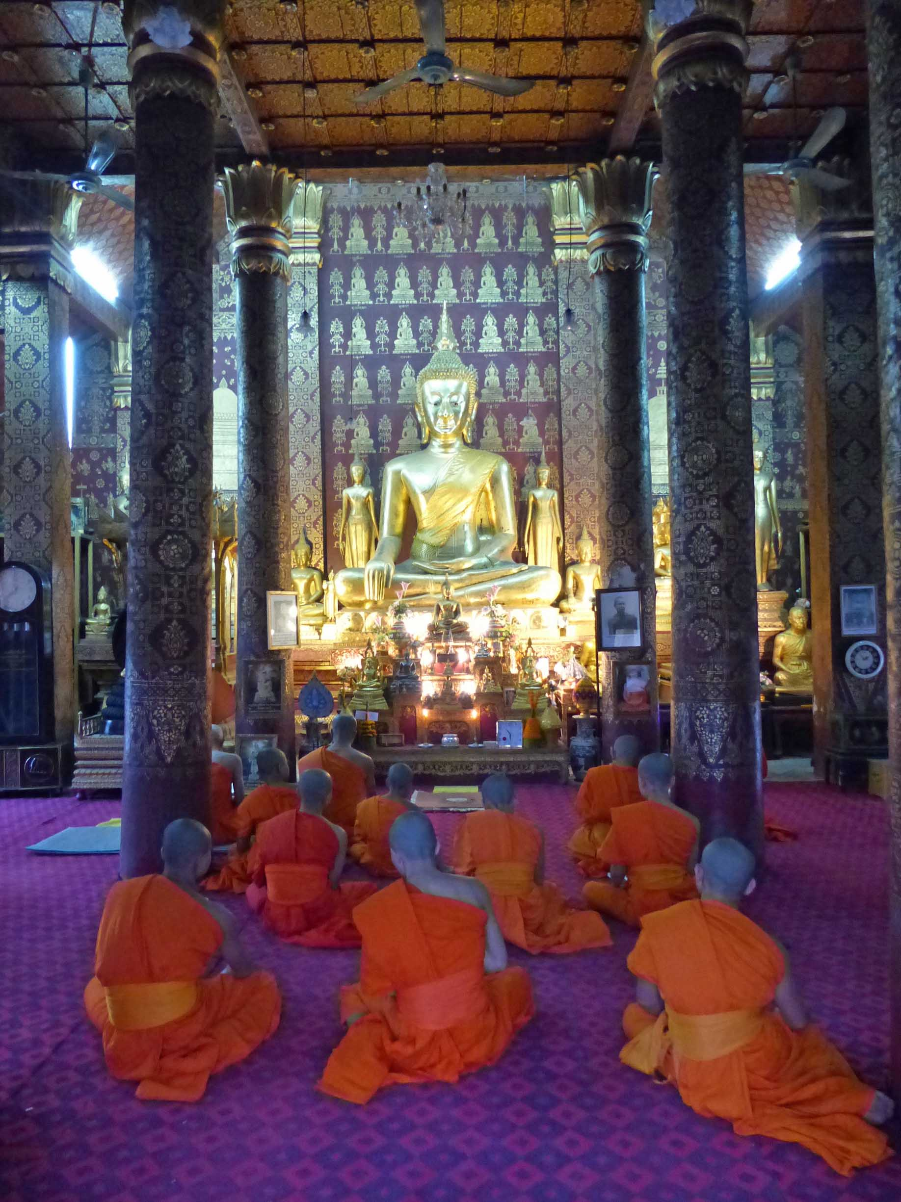 Young men in orange robes seated on the floor of a temple with large golden Buddha