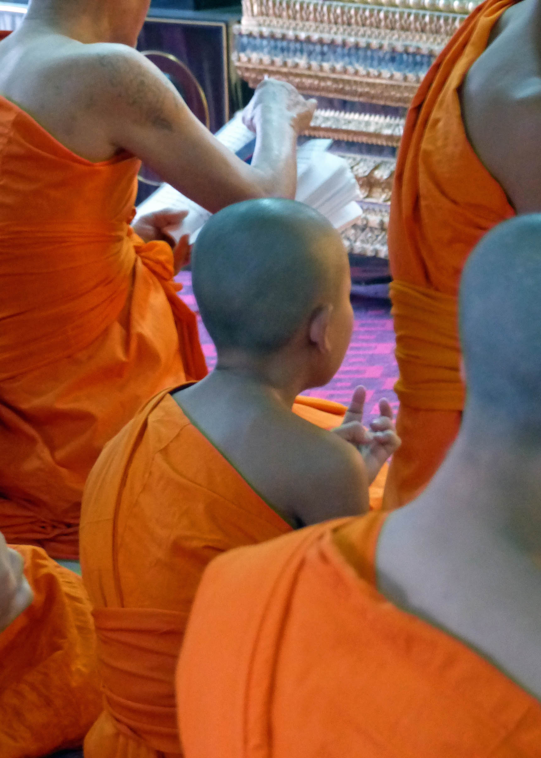 Young men in orange robes seated on the floor of a temple