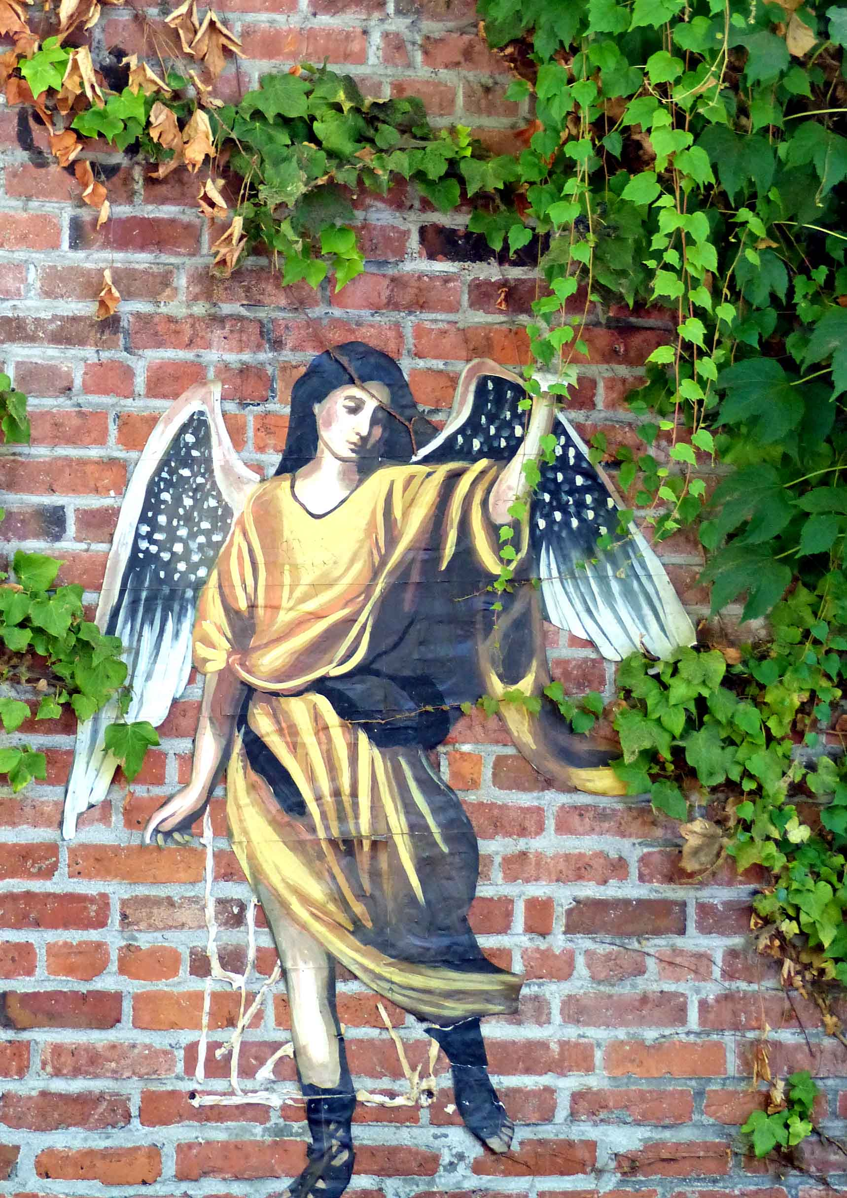 Mural of angel in yellow robe and black boots