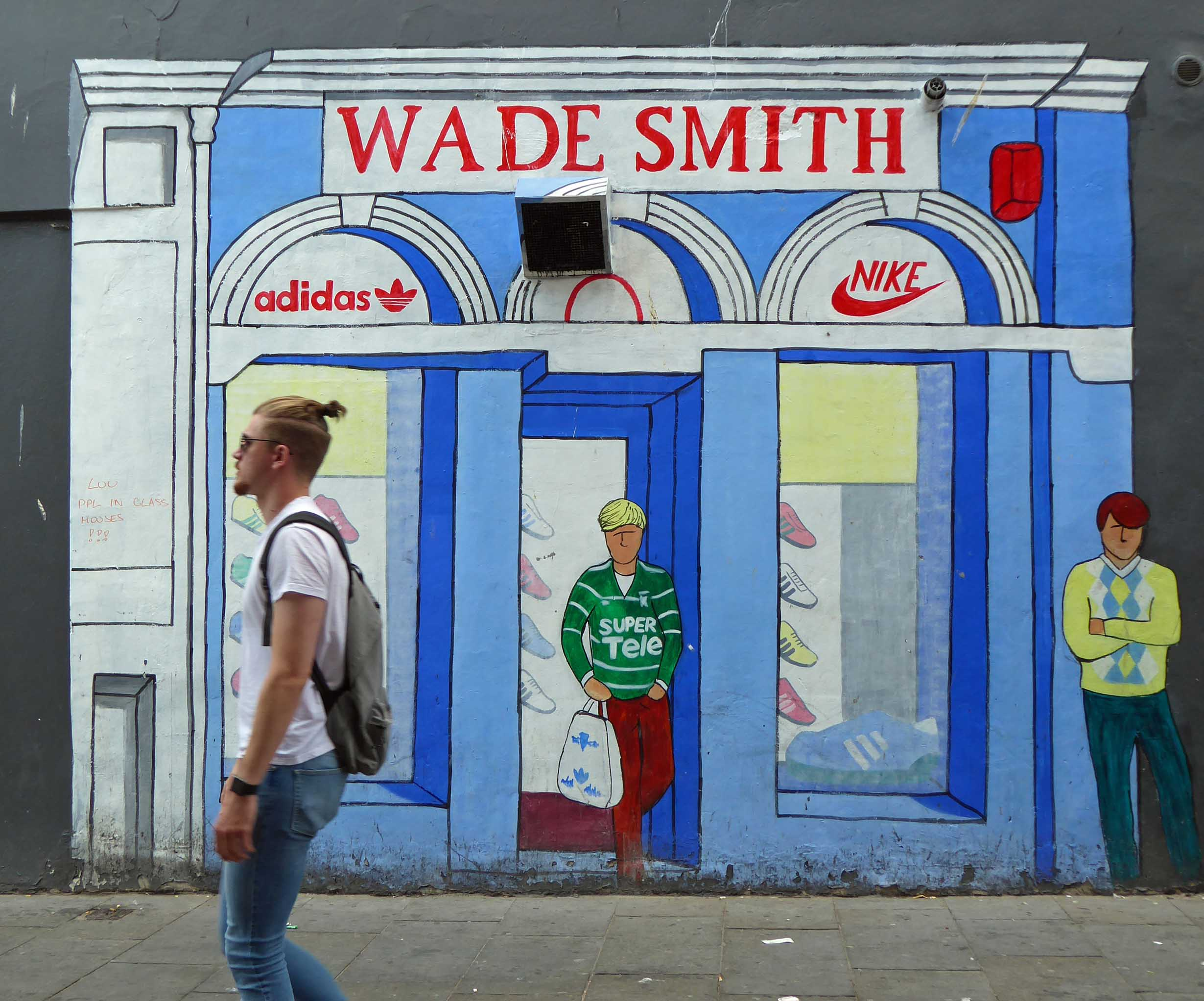 Mural of a sports shop frontage with man passing
