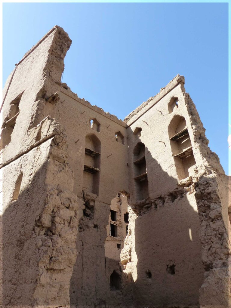 Looking up at ruined adobe houses