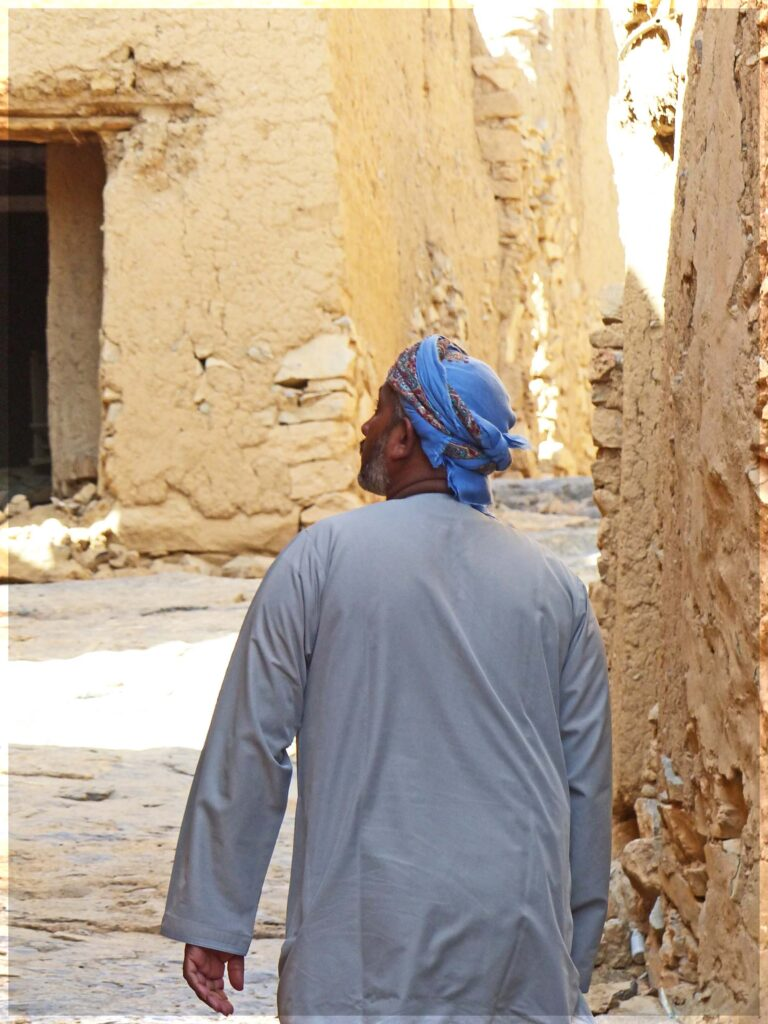 Man in white robe and blue turban walking through village