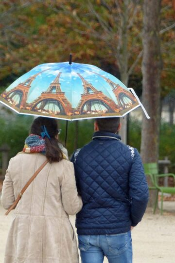 Couple with umbrella decorated with Eiffel Tower images