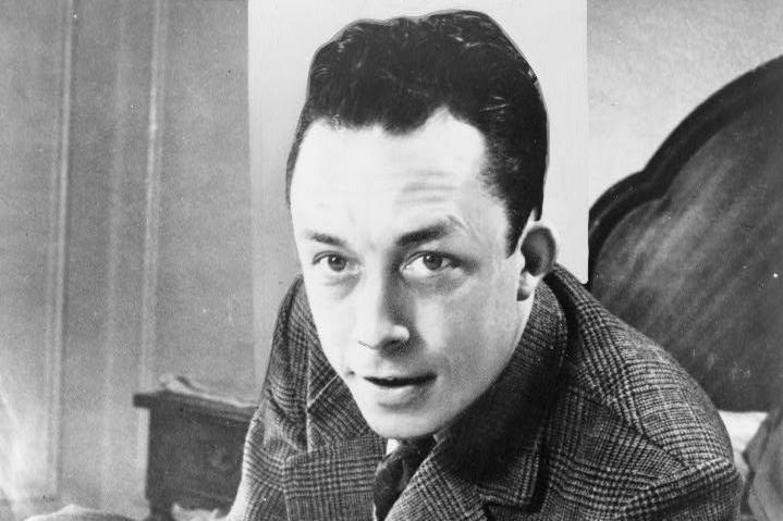 Albert_Camus_gagnant_de_prix_Nobel_portrait_en_buste_posé_au_bureau_faisant_face_à_gauche_cigarette_de_tabagisme1.jpg
