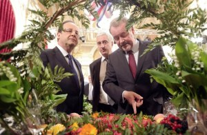 """""""I think I've found the solution, Sir."""" President Hollande looks pensive at a May Day Celebration of the Lily-of-the-Valley in Paris."""