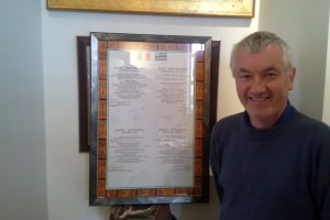 """""""I wouldn't have thought of driving in France 10 years ago but it's second nature to me now."""" Dunmanway-Quéven Twinning treasurer Stephen Daly stands before the framed signed twinning charter"""