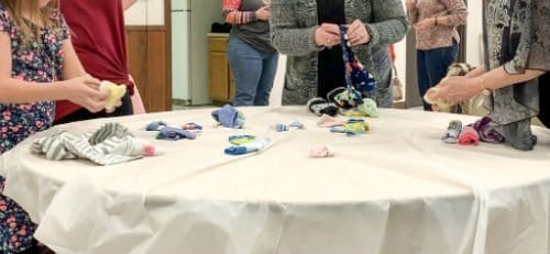 Women sorting baby socks on a table at a baby shower as a tie breaker game