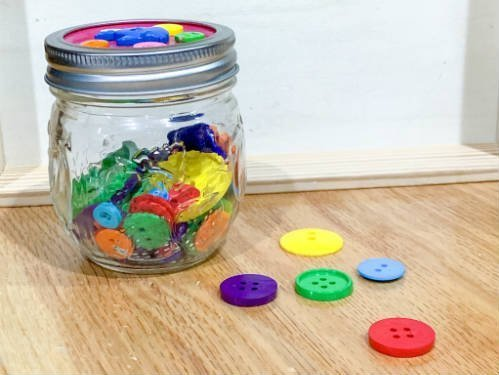 A small mason jar of buttons used as a tie breaker game for baby showers