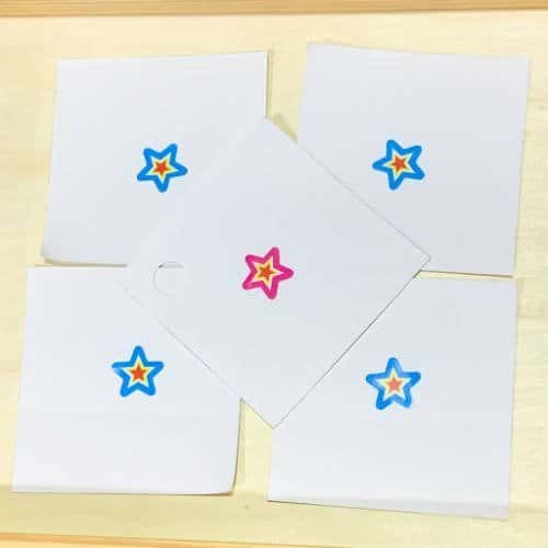 Five small pieces of paper with a star sticker on each. Four stars are blue and one star is pink. Whoever picks the pink star wins the tie breaker.