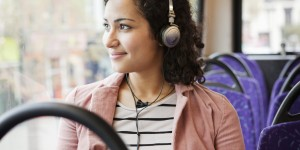 Woman sitting in bus listening to music.