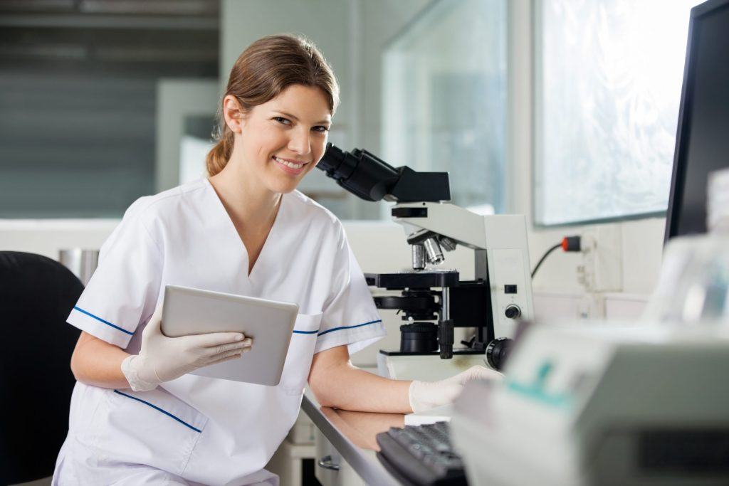 Portrait of happy young female scientist holding digital tablet in lab