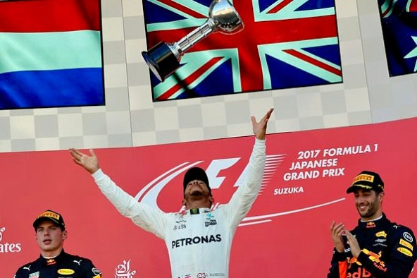 Mercedes driver Lewis Hamilton of Britain throws his trophy aloft as he celebrates after winning the Japanese Formula One Grand Prix at Suzuka, Japan, Sunday, Oct. 8, 2017. Second placed Red Bull driver Max Verstappen of the Netherlands, left, and his teammate Daniel Ricciardo of Australia, right, was third. (AP Photo/Eugene Hoshiko)