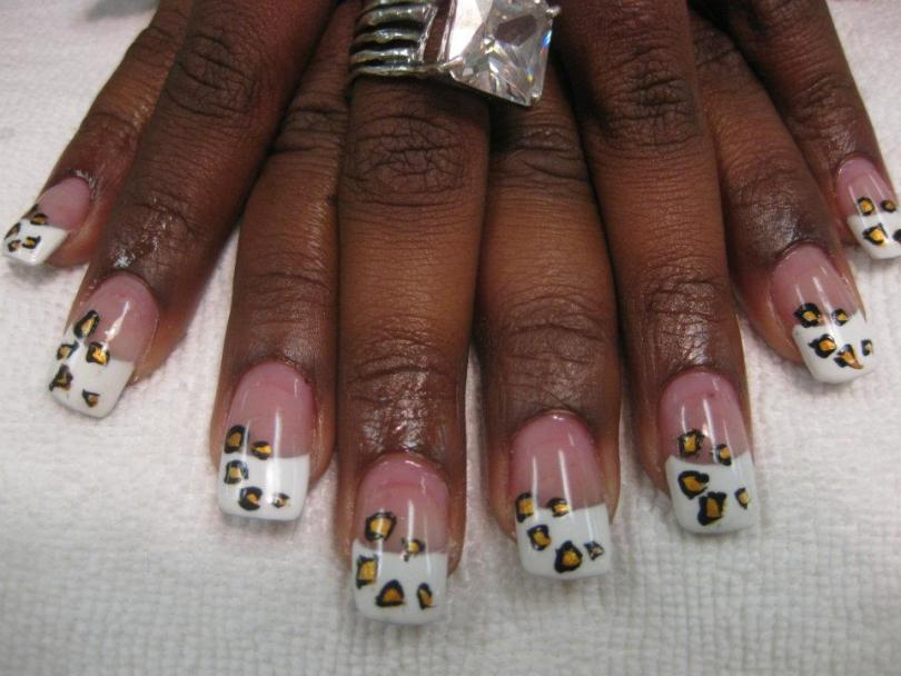 Pure white tip topped by flesh colored nail with five leopard spots (black around gold).