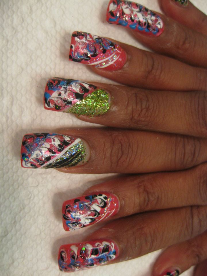 Blue/white/black intermixed swirls on either angled pink tip topped with sparkling green or full pink nail.