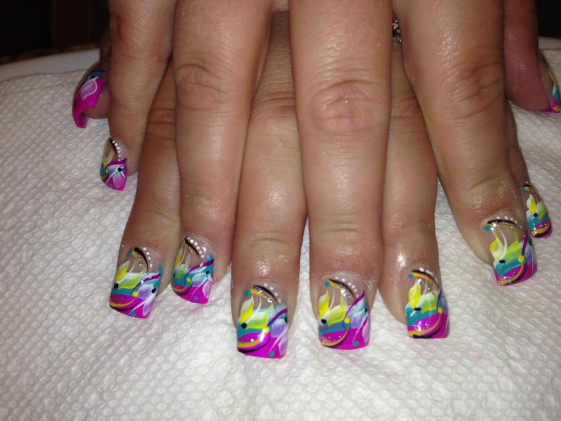 Slightly angled bright pink tip below aqua band topped with lavender/yellow lily petals, black/pink/orange/sparkly swirls, white/blue/yellow/black dots.