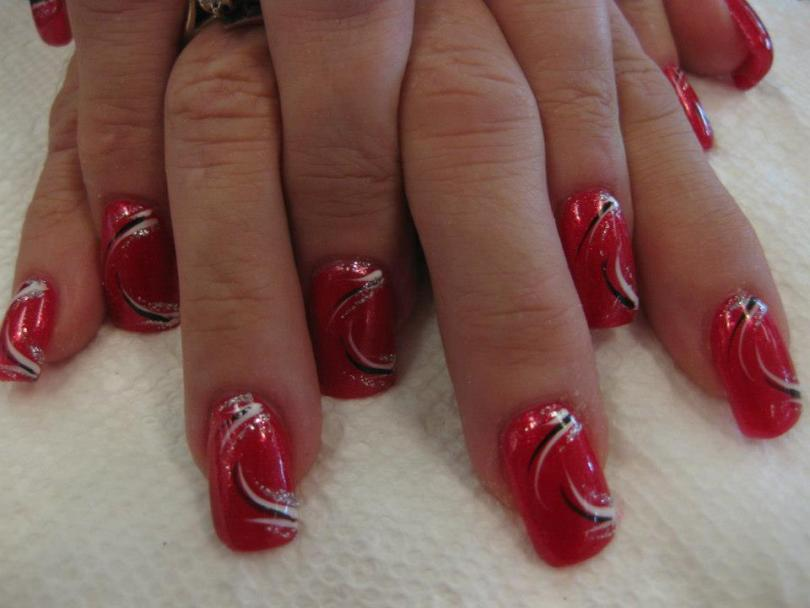 Full sparkling red nail with white/black/sparkly swirls top and bottom of nail.