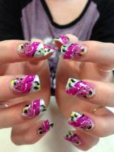 Angled sparkling silver tip under angled bright pink band, topped by translucent pink band, white/black swirls, white/pink/yellow/purple/black dots.