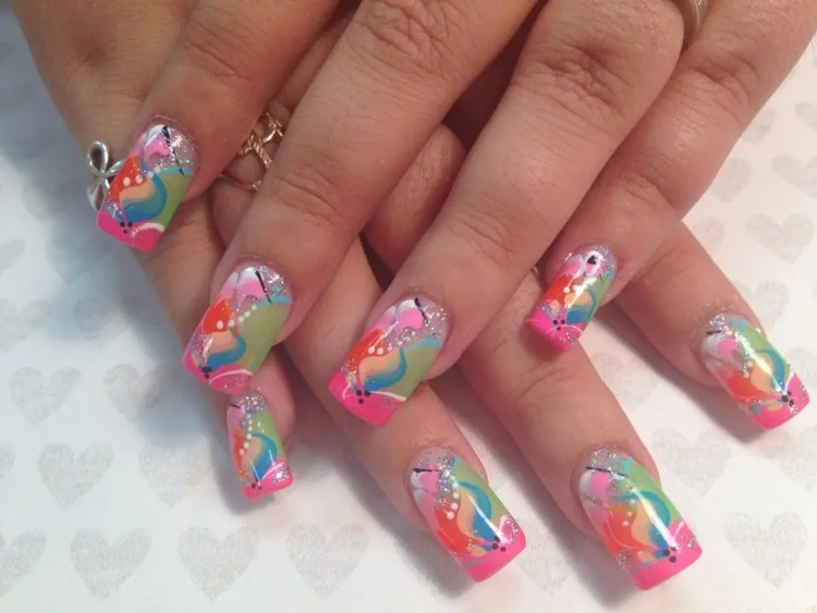 Bright pink tip under angled light green/orange halves with blue/peach swish in center, white/black/blue swirls, sparkles, pink/white swish at top.