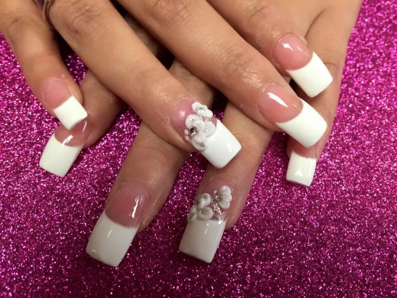 Classy long beautiful opaque white tips, flesh colored nail, choice of glue-on white flower petals with diamond centers.