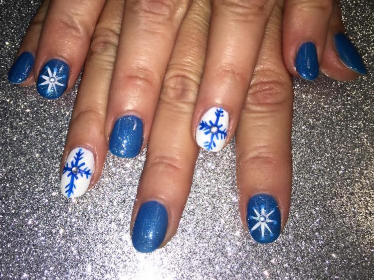 Sparkly bright blue nail w/eight-pointed star, diamond glue-on center, blue dots OR brilliant white nail w/bright blue snowflake, diamond glue-on.