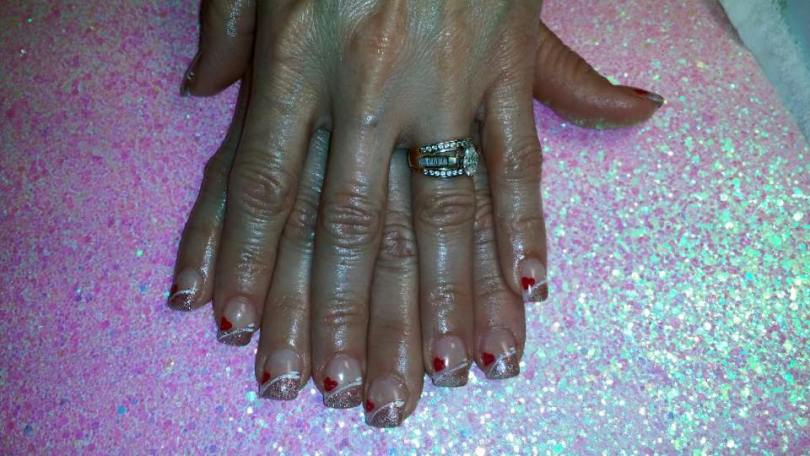 Angled sparkly pink tip topped with angled brilliant white line, one red heart, flesh colored nail.