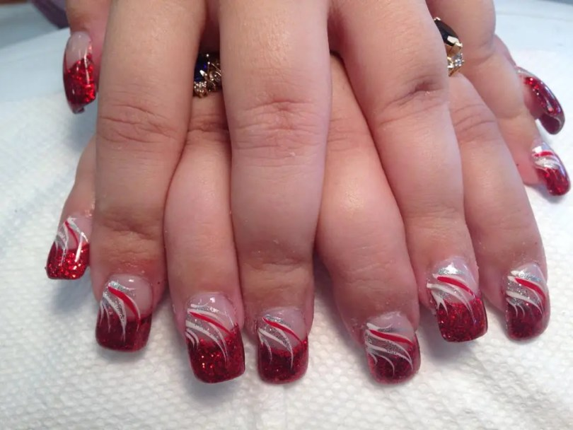 Sparkly bright red tip, flesh colored nail, white/red/silver swirls, sparkles.