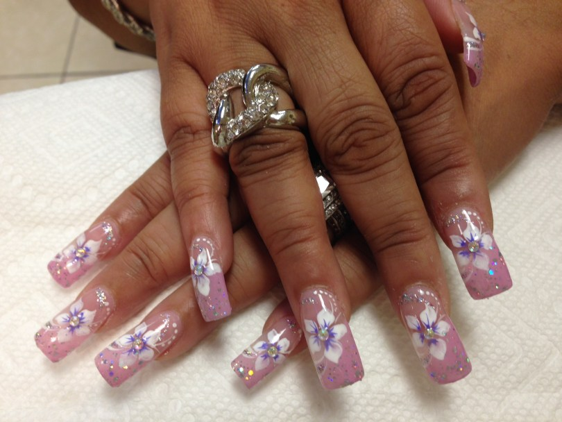 Light pink nail with white/lavender stargazer lily, diamond glue-on center, mirrored glue-ons on tip, white dots, sparkles.