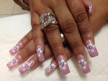 Light pink nail with white/lavender stargazer lily, diamond glue-on center, mirrored glue-ons on tip, white dots, sparkles.