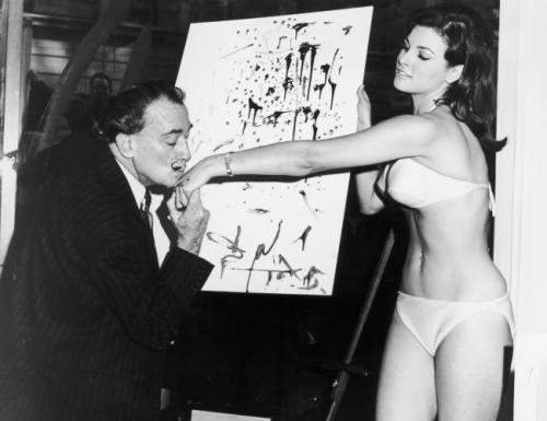 Сальвадор Дали целует руку актрисе Ракель Уэлч на фоне ее абстрактного портрета, 1965.