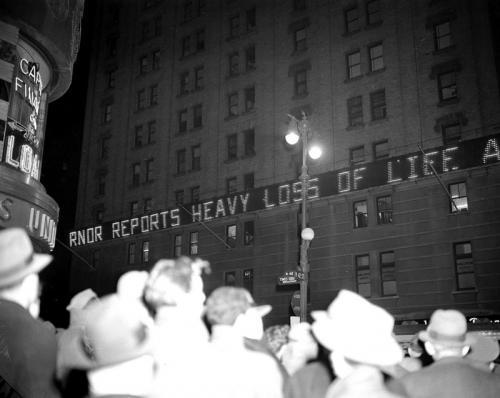 Толпа читает новости на электронном табло на Нью-Йорк-Таймс-билдинг в Нью-Йорке, 7 декабря 1941 года