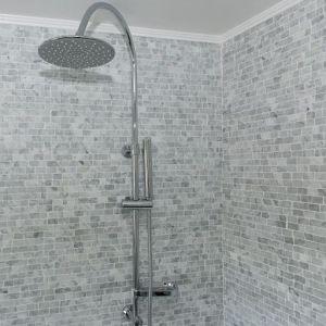Kleine carrara mozaiek voor de douchewand.