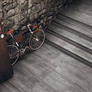 Een trap uitgewerkt in 2cm dik grijze houtlook tegels. Hier in combinatie met steenstrips.