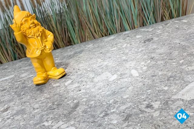 grijze ceppo terrastegels in combinatie met een gele tuinkabouter