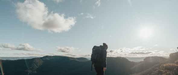 anonymous traveler walking on mountain peak