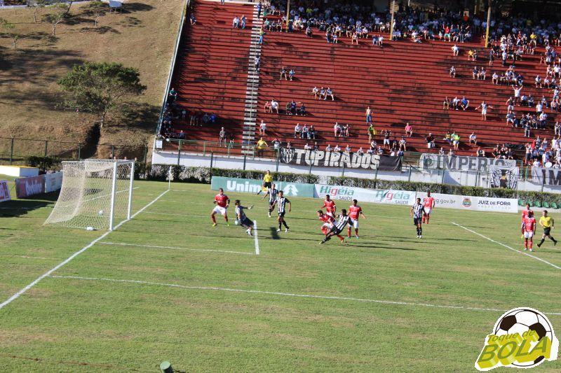 Depois do chute de Elder Santana, bola estufa a rede para o primeiro gol do Tupi e sai para a comemoração.