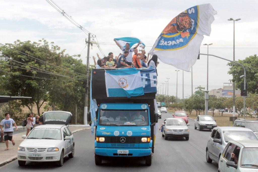 Delegação comemora título em cima de trio elétrico com bandeirão, medalhas e troféu. Foto: Bruno Campos