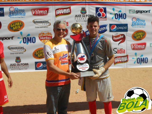 Vitor recebe o troféu de campeão para o América do Progresso