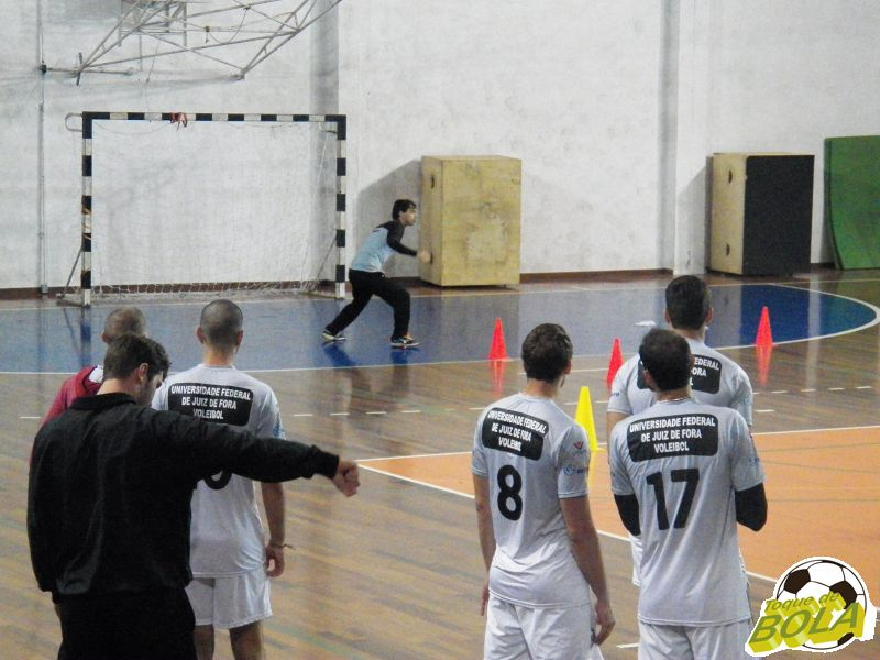 Bernardo, no fundo, explica circuito aos atletas em início de treino físico no ginásio da Faefid