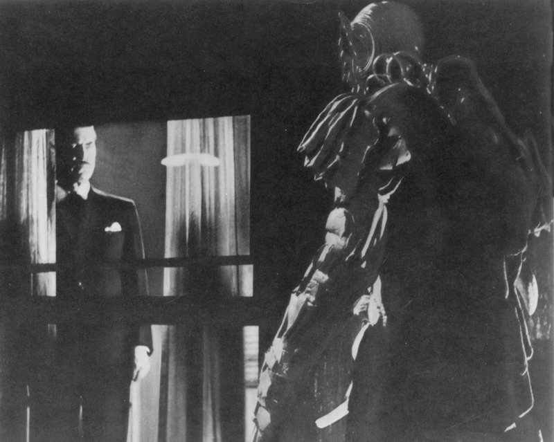 Edward L. Cahn, director, The She-Creature, 1956, motion picture, AIP.  A baleful Dr. Lombardi (Chester Morris) summons the She-Creature (Paul Blaisdell) from inside the home of millionaire businessman Timothy Chappel (Tom Conway). Exploiting a series of gruesome murders, Chappel catapults hypnotist Lombardi into a state of national celebrity. Click to enlarge.