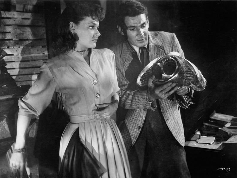 Sylvia van Buren (Ann Robinson) and Clayton Forrester (Gene Barry) look at a Martian electronic probe after Forrester has severed it from the metal stalk on which it was attached.  The probe was released through a door in the underbelly of a Martian war machine during a tense scene in George Pal's film version of The War of the Worlds. Click to enlarge.